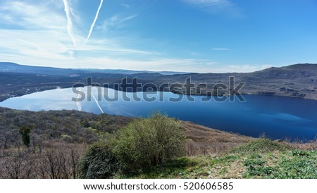 Ultra wide angle view of entire Sanabria lake with plane trail in Spain