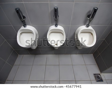 Ultra wide top view of 3 white automatic ceramic urinals on Grey tiled wall in an public toilet - stock photo
