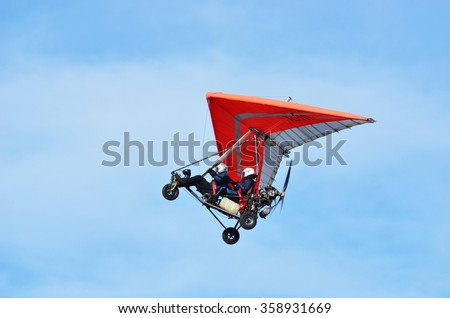 Ultralight trike flying with a pilot and a passenger against mountains - stock photo