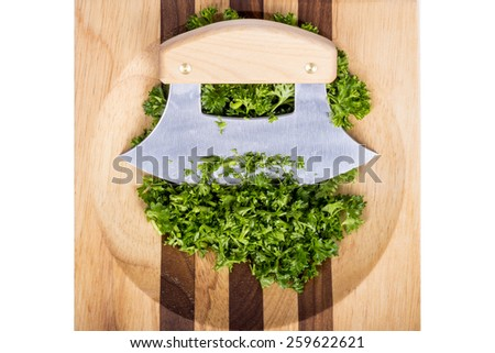 Ulu and Chopped Parsley Sitting on a Wooden Block  - stock photo