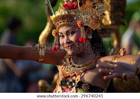 ULUWATU, BALI - CIRCA January 2011 - A woman dances during a traditional Kecak Fire Dance ceremony at the Uluwatu Temple. The ancient Hindu temple features ocean cliff views and wild monkeys. - stock photo
