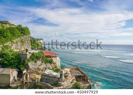 Uluwatu blue point coastline with beautiful rocky cliffs and turquoise wavy sea - stock photo