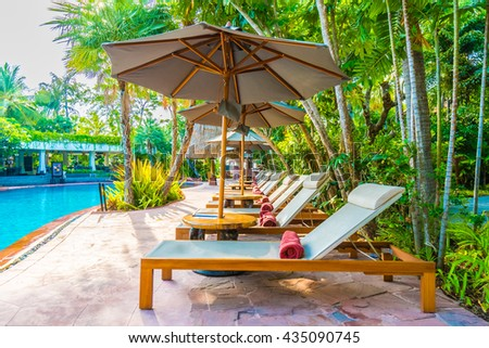 Umbrella and chair around outdoor swimming pool in hotel resort - Holiday vacation background concept - Boost up color Processing