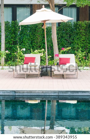 Umbrella and chair deck in hotel resort swimming pool - Filter effect