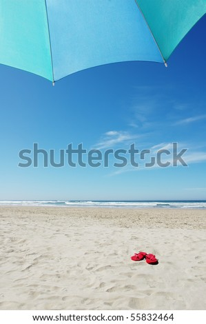 Umbrella and Red Flip Flops on Beach - stock photo