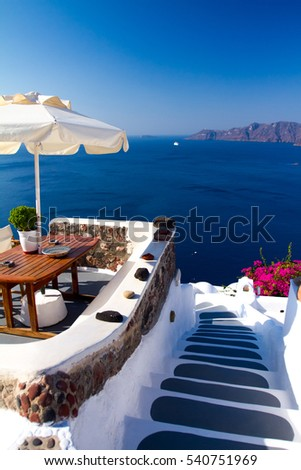 Umbrella and table with views of the sea and the volcano. White picket fences and classic Greek buildings in the background of the blue sky and the Cyclades. The Island Of Santorini. I love Greece!