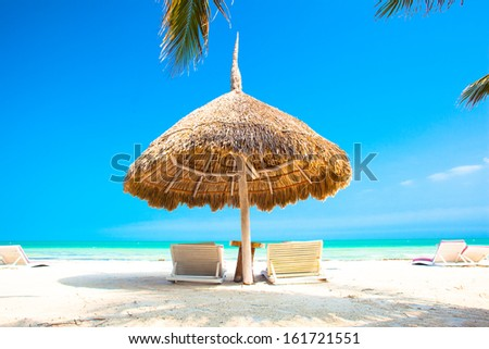 umbrella and two chairs on perfect Holbox beach - stock photo