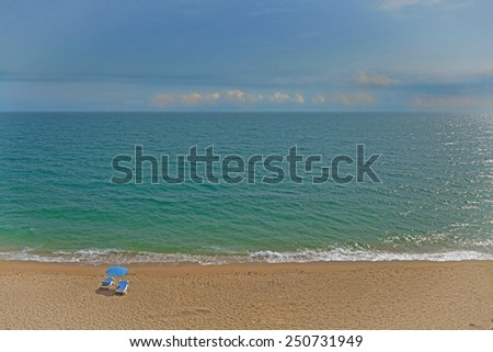 umbrella and two deck chairs on the beach. picture in retro style - stock photo