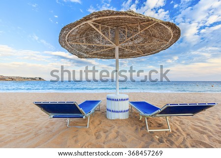 Umbrella and two empty deckchairs on the shore sand beach - stock photo