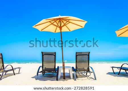 Umbrella beach chair on beautiful tropical beach - stock photo