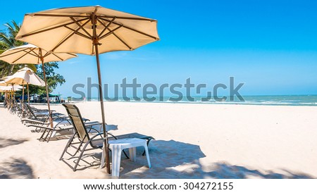 Umbrella bed deck on tropical beach with blue sky - stock photo