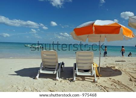 Umbrella Chairs on the Beach - stock photo