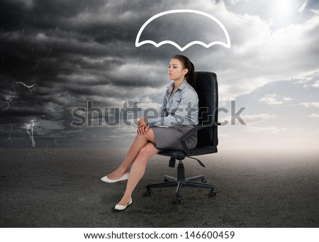 Umbrella graphic above the head of a businesswoman in stormy weather setting - stock photo