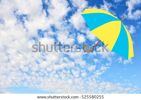 Umbrella in Ukrainian flag colors flies in sky against of pure white clouds.Mary Poppins Umbrella.Wind of change concept.
