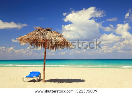 umbrella of palm leaves and blue deck chair on sand beach