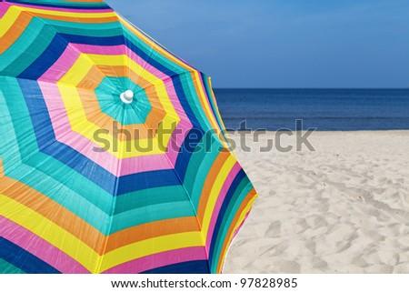 Umbrella on a sandy beach, summertime - stock photo