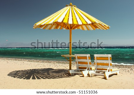 Umbrella on beach with chairs - stock photo
