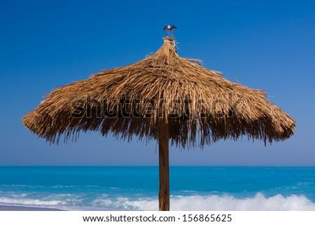 Umbrella on the beach on the  Ionian island of Lefkas Greece - stock photo