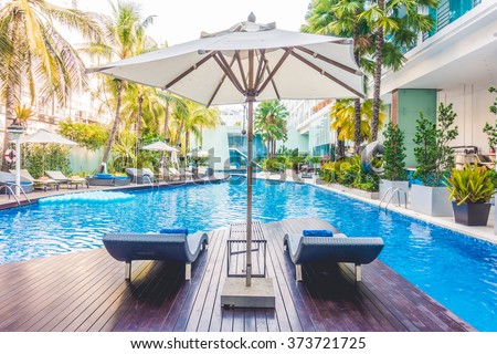 Umbrella pool and chair around beautiful luxury swimming pool in hotel resort - Vintage Light film Filter