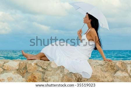 Umbrella sitting coast sitting girl in summertime - stock photo