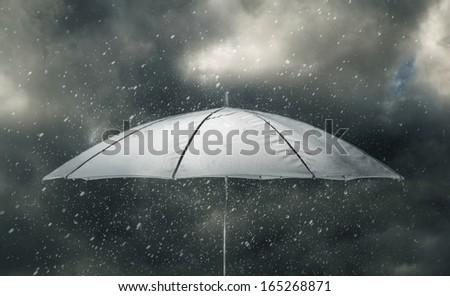 Umbrella under raindrops of thunderstorm - stock photo