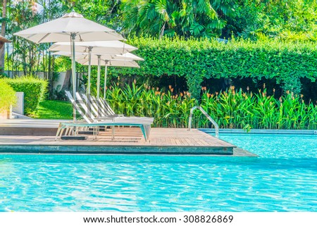 Umbrella with chair in hotel  swimming pool resort - stock photo