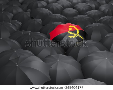 Umbrella with flag of angola over black umbrellas - stock photo