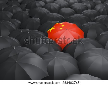 Umbrella with flag of china over black umbrellas - stock photo