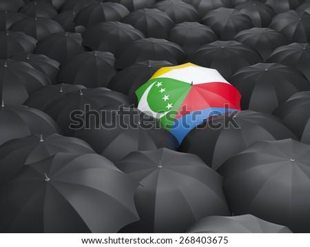 Umbrella with flag of comoros over black umbrellas - stock photo