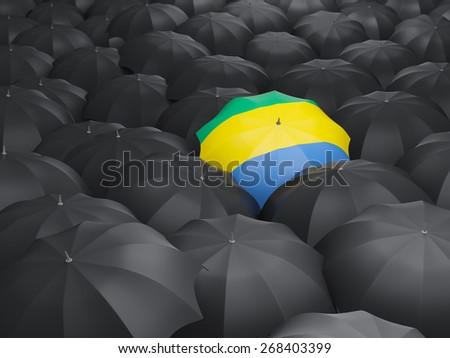 Umbrella with flag of gabon over black umbrellas - stock photo