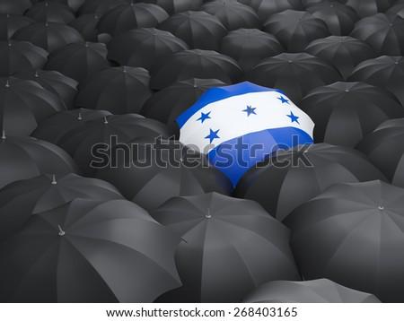 Umbrella with flag of honduras over black umbrellas - stock photo
