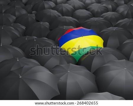 Umbrella with flag of mauritius over black umbrellas - stock photo