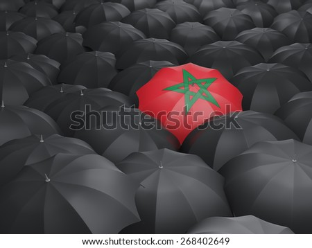 Umbrella with flag of morocco over black umbrellas - stock photo