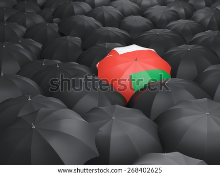 Umbrella with flag of oman over black umbrellas - stock photo