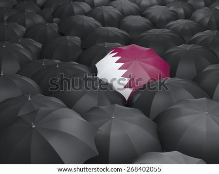 Umbrella with flag of qatar over black umbrellas - stock photo