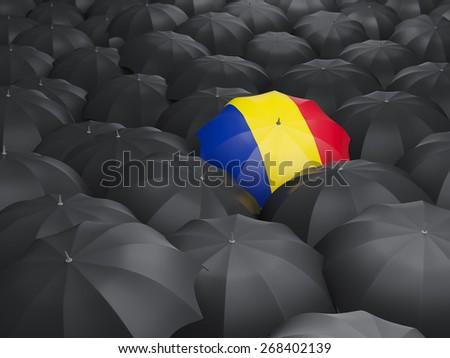Umbrella with flag of romania over black umbrellas - stock photo