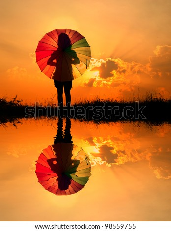 Umbrella woman and sunset silhouette,Water reflection - stock photo