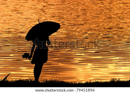 Umbrella woman holding multicolored umbrella silhouette in Lake