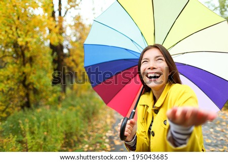 Umbrella woman in Autumn excited under rain on fall day.Beautiful young female wearing raincoat surprised and excited in the rain. Mixed race Asian Caucasian girl in her 20s walking in forest. - stock photo