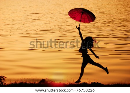 Umbrella woman jump and sunset silhouette in Lake - stock photo