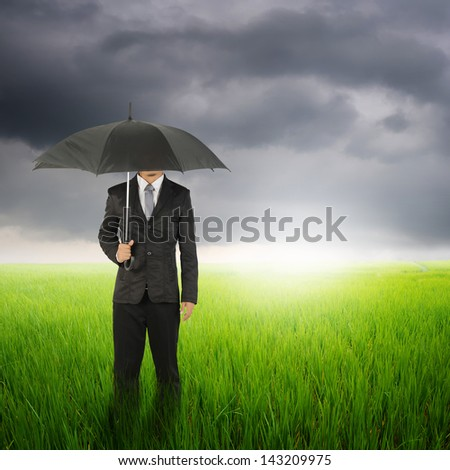 Umbrella woman standing to raincloud in grassland with  umbrella