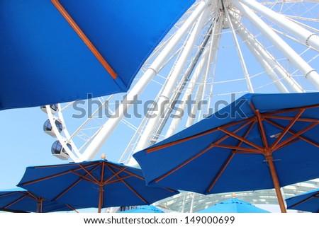 Umbrellas and Ferris Wheel - stock photo