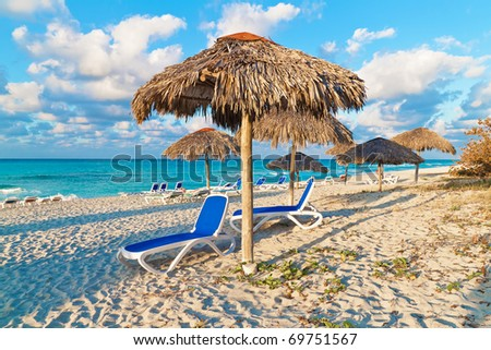 Umbrellas and reclining beds on a beautiful tropical beach in Cuba