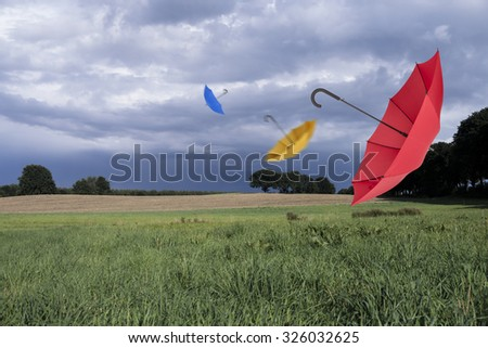 Umbrellas and storm clouds - stock photo