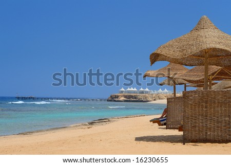 Umbrellas on the golden beach and the white seafood restaurant on horizon - stock photo