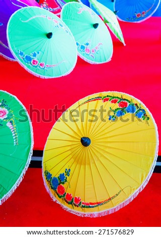 Umbrellas, oriental decorative multicolor, vertical image, over red background - stock photo