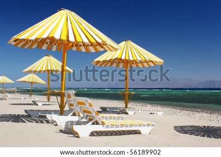 Umbrellas with chairs on beach near blue sea - stock photo