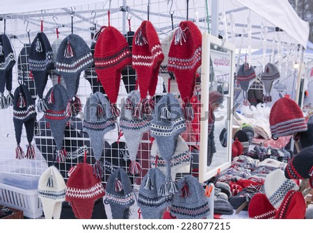 UMEA, SWEDEN ON DECEMBER 08. Christmas market, handicraft for sale on December 08, 2013 in Umea, Sweden. Woolen hoods in an outdoor stall for sale. Unidentified people. - stock photo