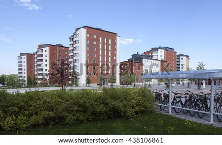 UMEA, SWEDEN ON JUNE 02. View of buildings, apartments from opposite side a street on June 02, 2016 in Umea, Sweden. Park and shelter for bicycles this side.  - stock photo