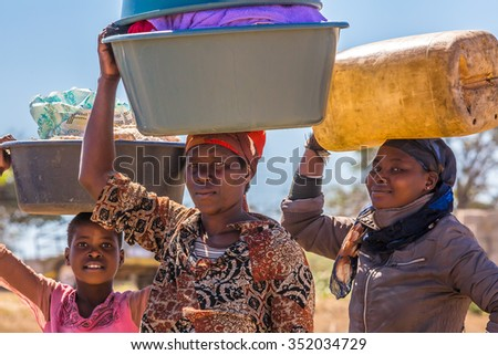 UMkhuze Game Reserve, South Africa - August 24, 2014: African women go to wash their clothes in the river, carrying basins on their heads